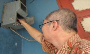 Gunawan, warga di Jl. Kartini, Rembang, menghidupkan meteran listrik.