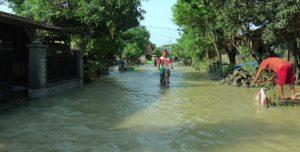 Jalan kampung Desa Kuangsan berubah menjadi seperti sungai. (gambar atas) warga mengevakuasi sepeda motor pengguna jalan yang terseret banjir di jalur Kuangsan – Pengkol, Rabu pagi.