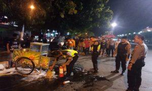 Petugas Sabhara Polres Rembang memadamkan api di dalam gerobak Cilok Edun, Sabtu malam.