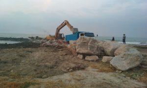 Operator alat berat beckhoe menata batu – batu besar untuk pemecah gelombang.