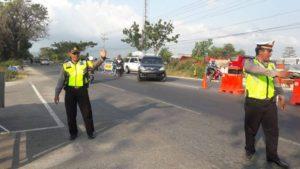 Polisi mengatur lalu lintas di jalur Pantura, dekat pintu masuk menuju Pantai Karangjahe Rembang.