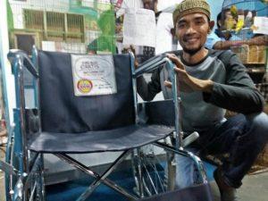 Dimas Totok menunjukkan kursi roda gratis yang akan disalurkan kepada penyandang disabilitas.