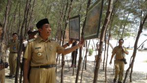 Bupati Rembang, Abdul Hafidz mengamati lukisan yang dipamerkan di pinggir Pantai Pasir Putih Dusun Wates, Senin (23/07).