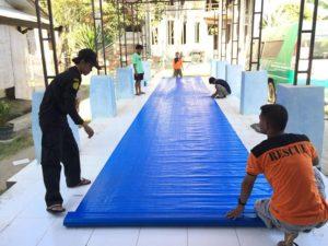 Syaiful Halim (kaos orange), relawan dari Ubaloka Rembang memotong terpal, untuk keperluan tenda pengungsi gempa bumi di Lombok.