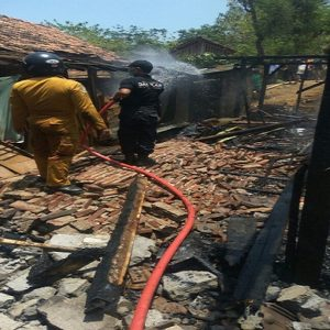 Petugas pemadam kebakaran menyemprotkan air saat kebakaran di Desa Karangasem, Kecamatan Bulu. Pasca kejadian, warga kerja bhakti, Jum'at sore.