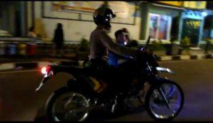Anggota Satuan Sabhara Polres Rembang menggiring seorang pengendara motor yang diduga ikut balapan liar di Jl. Dr. Wahidin Rembang, Sabtu malam.