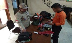 Syaiful Halim (kaos orange) dan Bagas Eka Adi Haningtama, dua relawan dari Rembang yang dikirim ke lokasi bencana tsunami Selat Sunda. Keduanya menyiapkan perbekalan, Senin siang (24/12).