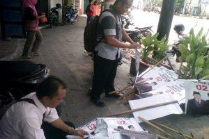 Petugas Panwas Kecamatan Rembang Kota menertibkan alat peraga kampanye Prabowo – Sandi di dekat bundaran Pasar rembang, Jum'at (11/01).