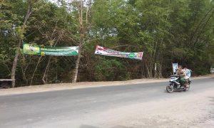 Warga Desa Sidorejo, Kecamatan Sedan melintas di dekat alat peraga kampanye Pemilu 2019.