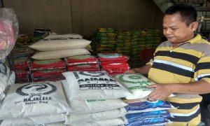 Pedagang di sebelah timur Pasar Rembang, Gampang Haryono menata tumpukan beras di tokonya, Minggu (13/01).
