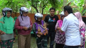 Ketua Umum GRIND, Kuntum Khairu Basa membagikan helm kepada warga di Desa Sluke, Kecamatan Sluke.