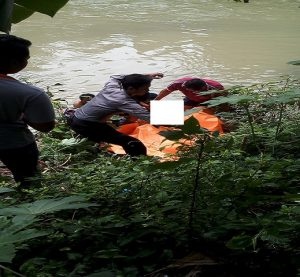 Polisi dibantu warga mengevakuasi jenazah korban, dari Sungai Bagan Lasem, Sabtu pagi (09/03).