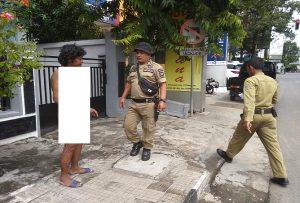 Petugas Satpol PP mengamankan wanita telanjang bulat di depan Kantor Bupati Rembang, Senin pagi (29/04).