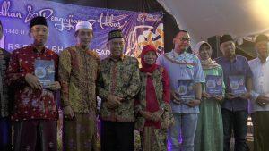 Buku Biografi Atna Tukiman diluncurkan. (Gambar atas) Atna Tukiman bersama isteri menyerahkan buku biografi kepada salah satu putrinya, Sabtu malam (11/05).