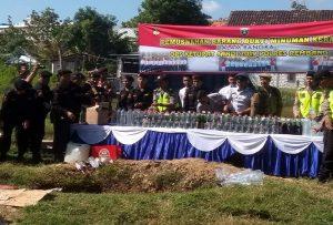Pemusnahan ribuan botol Miras di selatan Mapolres Rembang. (foto atas) Kapolres Rembang, AKBP Pungky Bhuana Santosa menunjukkan botol minuman berenergi yang diisi arak, Selasa (28/05).