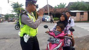 Kanit Dikyasa Satlantas, Aiptu Hartono saat giat operasi. (Gambar atas) Kasat Lantas Polres Rembang, AKP Roy Irawan membawa tanda gambar, untuk mengingatkan pengendara motor memakai helm.