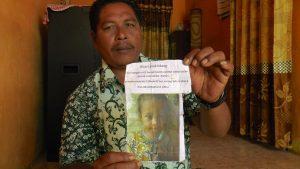 Nurjahid menunjukkan foto keponakannya, Alfi Khairunafiah. (Foto atas) Saat kangen, sang ibu sering melihat baju kesukaan Alfi.