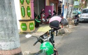 Pengemudi ojek online mangkal di gapura masuk gang I Tawangsari, Rembang, Kamis (11/07).