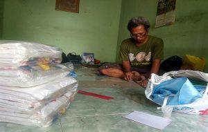 Suntari tampak sibuk menyelesaikan pesanan sablon di rumahnya, dekat pertigaan Jeruk, Sendangagung, Kaliori.