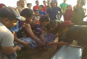 Polisi bersama warga mengevakuasi jenazah korban di TKP belakang kantor Satpol Air & Pos AL Pelabuhan Tasikagung, Minggu (29/09).