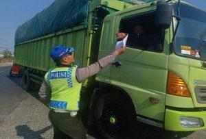 Anggota Satlantas Polres Rembang membagikan selebaran kepada sopir kendaraan berat, terkait rencana penutupan jalur Pantura.
