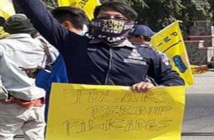Seorang mahasiswa di Rembang membawa poster tolak Perbup Pilkades. (Foto atas) Hasil revisi Perbup menunjukkan adanya tes tertulis.