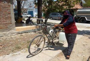 Warga Desa Banggi Petak Kecamatan Kaliori mendorong sepeda, usai mengambil air bersih.