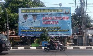 Seorang warga di Rembang melintas di dekat baliho tentang daerah tertib ukur, Jum'at (25/10).
