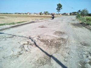 Seorang pengendara sepeda motor melintas di jalan lingkar Tireman – Weton yang rusak parah, Minggu (10/11).