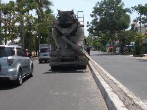 Pekerja menutup lubang di sela-sela median pembatas dengan cor beton.