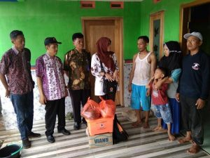 Petugas BPBD Kab. Rembang menyerahkan bantuan kepada korban bencana angin puting beliung, yang kini menumpang di rumah tetangga, Kamis (12 Desember 2019).