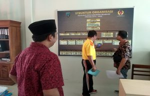 Wakil Bupati Rembang, Bayu Andriyanto (baju merah) mengamati susunan pengurus KONI yang lama, saat mengantarkan isterinya mendaftarkkan diri di Sekretariat KONI Kab. Rembang, Minggu (15/12).