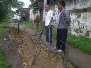 Anggota Komisi III DPRD Rembang, Jasmani yang juga warga Desa Gedongmulyo, Kecamatan Lasem mengecek jalan longsor di pinggir Sungai Bagan, Senin pagi (24/02).