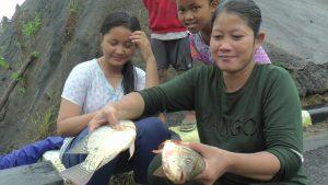 Warga menunjukkan ikan yang diperoleh dari limpasan Waduk Panohan. (Gambar atas) Sejumlah pemuda menghadang ikan di bawah limpasan air waduk, Kamis (20/02).