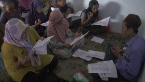Ibu-ibu warga Desa Waru, Rembang membaca Asmaul Husna, sebelum pencairan pinjaman. (Foto atas) Warga menunjukkan uang hasil pinjaman dari Bank Waqaf Mikro, Kamis (12/03).
