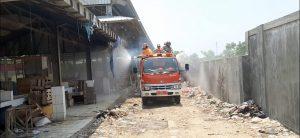 Petugas Damkar Rembang menyemprot cairan desinfektan ke area los pasar, Senin (30/03).