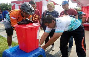 Usai bersepeda, pihak panitia menyediakan sarana cuci tangan. (Foto atas) Dokter memperagakan cara mencuci tangan yang benar dari atas panggung, Minggu (15/03).