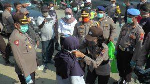 Polwan Polres Rembang mengenakan masker kepada warga di Desa Tasikagung. (Foto atas) Kapolres Rembang, AKBP Dolly A. Primanto mendorong kursi roda penyandang disabilitas di Alun-Alun, usai menyerahkan paket Sembako, Sabtu (04/04).