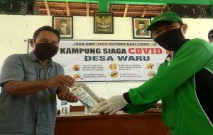 Ketua HAKLI Kabupaten Rembang, Al Furqon (bertopi) menyerahkan bantuan hand sanitizer kepada Kepala Desa Waru, Daryono.