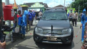 Mobil Kapolres Rembang disemprot disinfektan, saat akan masuk Desa Ngotet.