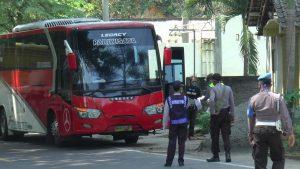 Petugas gabungan menghentikan bus di depan posko pemeriksaan terpadu Covid-19 perbatasan Rembang – Blora. (Foto atas) Bupati Rembang, Abdul Hafidz diperiksa suhu badannya oleh petugas posko, Kamis (16/04).