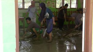 Guru SD N Ngulaan, Selasa siang (21/04) membersihkan lumpur di dalam ruang kelas. (Foto atas) Guru menunjukkan buku yang basah akibat terkena banjir.