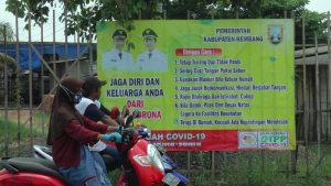 Warga berhenti di lampu pengatur lalu lintas Perempatan Mondoteko, Rembang. Tampak ada banner himbauan waspada Corona dari Pemkab Rembang.