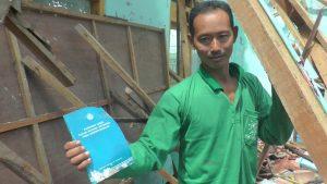Penjaga SD N II Babadan Kecamatan Kaliori menunjukkan buku perpustakaan di tengah-tengah puing bangunan yang ambruk, Minggu (10 Mei 2020).