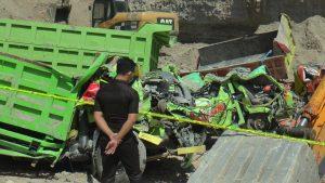 Seorang polisi mengamati dump truk yang rusak, akibat tertimpa material longsoran di lokasi tambang tras Desa Blimbing Kecamatan Sluke.