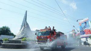 Mobil Damkar menyemprotkan disinfektan di ruas jalan kawasan bundaran Pasar Rembang, belum lama ini. Hari Sabtu (06/06) penyemprotan semacam ini masih terus berlanjut di ruas jalan lain.