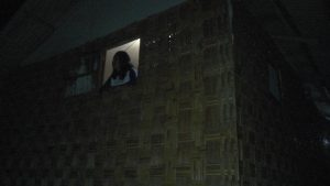 Kartini menikmati keheningan malam dari balik jendela gubuknya.