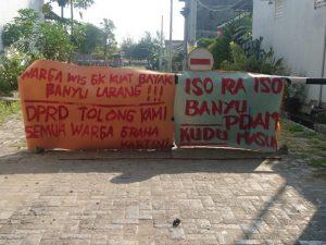 Poster tuntutan di pintu masuk menuju Perumahan Graha Kartini Rembang.