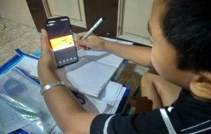 Seorang anak di Rembang, belajar online dengan menggunakan HP, Selasa (21/07).
