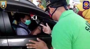Petugas Satpol PP Kabupaten Rembang mengecek pengunjung obyek wisata Pantai Karangjahe Rembang, sudah memakai masker atau belum.
